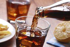 Ein Glas voll Cola vor einem Teller Pommes