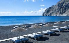 Bellonias Villas black sand hotel beach in Kamari, Santorini with sunbeds & umbrellas