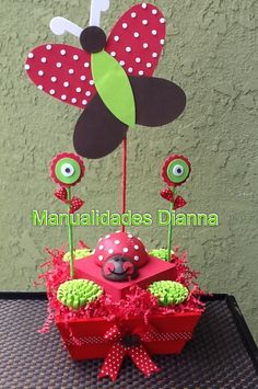 """For more information on this or other items, visit my Facebook page: www.facebook.com/CraftingPartiesByDianna  This Butterfly and Ladybug centerpice is all handmade out of EVA Foam material and styrofoam. The flowers are also made of EVA Foam and """"leaves"""" are made from ribbon. Everything is standing on a hand painted (with acrilic paint) box and wrapped with a ribbon."""