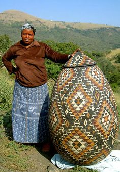 A Zulu weaver and her basket, from KwaZulu-Natal province in South Africa. Follow the link to a website that includes background information about the history and culture of Zulu people and of this still-practiced art form.