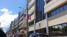 Calle San Jorge 12:00, en los postes de luz se encuentran las banderas de Puerto Rico y Estados Unidos, ambas banderas están mal puestas por que están mirando hacia abajo cuando la punta debe de ir hacia el frente. También la están utilizando como decoración u eso tampoco se permite.