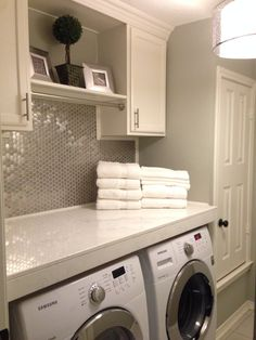 Comfortable yet modern style utility / laundry room with stainless backsplash tiles and white cabinets. Very clean look with stainless steel accents and sherwin williams 'mist gray' on the walls.  A great design for small compact laundry room