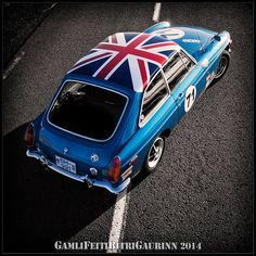 The backside of a 1971 MGB GT tricked out with a painted UK flag and racing number.
