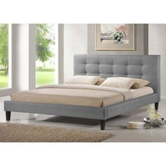 This queen-sized upholstered platform bed frame is made of both hardwood and MDF and is fully upholstered in grey linen with underlying padding.