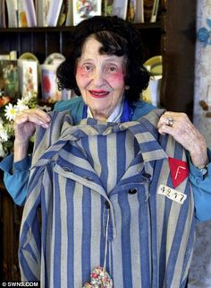 A 104-year-old Holocaust survivor holds up the concentration camp uniform she used to have to wear.