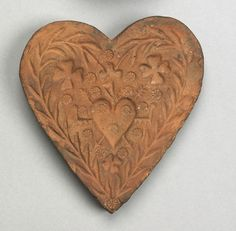 """Pook & Pook.  April 20th & 21st 2007. Lot 300.  Estimated: $400 - $600. Realized Price: $3042. Pennsylvania redware heart shaped, unglazed butterprint with vine, rosette, heart cut, and compass decoration, inscribed verso """"Jacob Berger"""", 5"""" h."""