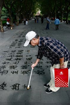 Practicing calligraphy on the ground using clear water as ink - also called 'Di Shu' in Chinese. Started in the 1990s, this activity was first founded in a park in the north of Beijing before spreading widely to other cities in China. You can find them in lots of parks in Beijing and Shanghai.