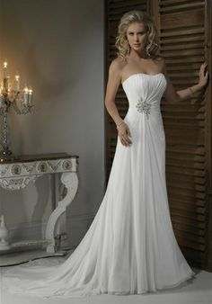 Strapless, slim line gown with dipped neckline and corset closure. Paris Chiffon is dramatically ruched, leading into a grand beaded motif at the side waist. This stunning jeweling is echoed at the back corset closure and finishes with a flowing gathered train.