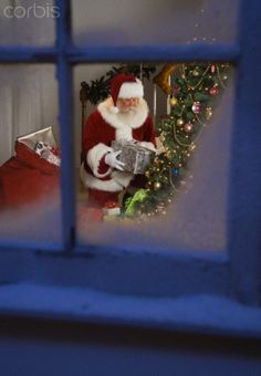 Santa Claus leaving gifts under Christmas tree