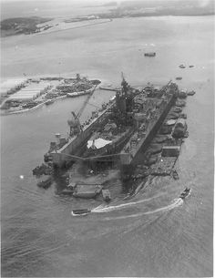 ABSD-3 at Guam, Marianas Islands & the Pennsylvania (BB-38) docked in ABSD-3 after the end of World War II. Note the white boxes on the barge, these are coffins that contain the remains of Pennsylvania crew members killed during the Kamikaze attack on her at Okinawa, 12 August 1945.