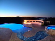 A pebbled stream with twinkling underwater lights flows from the hot tub to the pool in this dreamy outdoor oasis. A curved outdoor fire pit with semiciricle bench extends out from the stone deck, providing a spot to enjoy the stunning view.