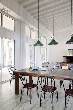 Living comedor integrado en una casa playera del barrio de Costa Esmeralda, con detalle de galponeras verde musgo y muebles de hierro.