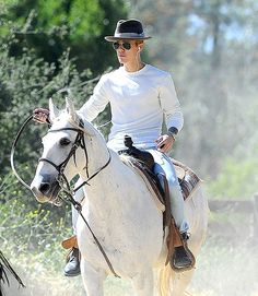 Justin Bieber played the role of cowboy on horseback, sporting the proper hat, classic aviator shades, a simple white top and blue jeans y'all!