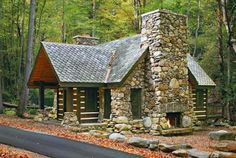 A playful arrangement of native stone with contrasting log and timber elements, the storybook cabin that follows is loaded with charm. Oversize stone chimneys anchor each end of this enchanting design from Johnson Architecture in Knoxville,Tennessee. Scalloped slate tiles cover the roof to enhance its fairy tale facade.