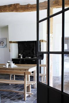 Kind of neat to see this combination of rough beams, light-coloured furniture with simple modern designs, white paint, and windows with dark frames (or in this case a door)