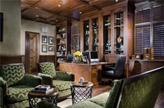 This massive home office has beautiful  woodwork throughout the room. The windows have wooden shades that blend easily with the imposing bookcases and cabinets. Green textured seating adds contrast, color and visual interest.