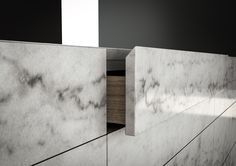 Monolith from piqu. A full stone kitchen island. Mitred edge details allows gaps between drawers to be kept to a minimum to accentuate the overall effect of one solid piece of stone.