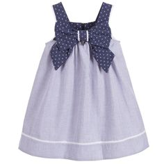 Girls blue and white striped dress from Lapin House. Made in seersucker cotton, the fabric has a mid-weight feel and is slightly ribbed. The top bodice has an anchor print, with a matching bow at the front and an attached silver heart charm. The dress fastens at the back with a concealed zip.