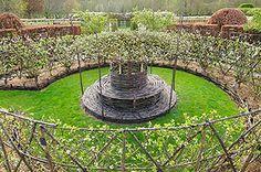Prieuré d'Orsan - Les Jardins: Le Labyrinthe Le labyrinthe, réalisé en pruniers palissés, est le symbole chrétien de la difficulté d'accéder au salut. Les cognassiers en éventail et poiriers en double spirales illustrent l'art du palissage fruitier.