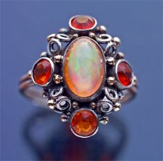 Dorrie Nossiter. Arts and Crafts ring. Silver, gold and opal, c. 1930. H: 2 cm (0.79 in). Original fitted case. An exceptional full play fire opal surrounded by cherry opals (orange fire opals). Original box marked: 'Dorrie Nossiter 40 Parliament Hill Mans. Lissenden Gdns. N.W.6. Tel: Gulliver 4201'. Sold by Tadema Gallery. View 1.