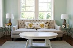 Inspiration for sunroom Tiek Built Homes - Caitlin Creer custom tufted sofa, blue wall paint colour, Pottery Barn blue smoke fringed hand-loomed rug, F Schumacher Avebury floral vine in citrine lumbar pillow, target lamps and brass round accent tables. Designed by Caitlin Creer Interiors.