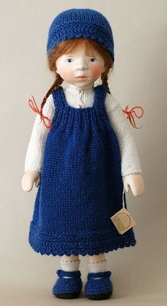 Girl in Blue Knit Jumper by Elisabeth Pongratz: Signature hand carved wood, poseable body, hand-painted features & a red mohair wig styled in pigtails. Ensemble entirely knit by hand. Elisabeth is from a time & culture where children were not showered with new dolls every year: they had one precious doll to play with throughout their childhood. Guided by this philosophy, she creates dolls to stand the test of time. Pongratz dolls are meant to be held, played with & cherished for a lifetime.