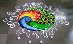 Rangoli using poster colors on floor - peacock design decorated with diya