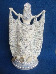 Linda imagem da Rainha do Mar.  Imagem de gesso, pintada em branco com prata e azul.  Observe que na rede, assim como na base da imagem foram aplicadas conchas e perolas.  Pessoalmente é ainda mais linda!