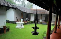 Rooms with veranda and hanging oil lamp, overlooking a green courtyard with Tulasi (holy basil) pedestal/platform for prayer, a typical Kerala architecture - iSpice Tours Team