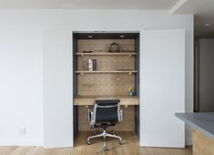 Office, Medium Hardwood Floor, Chair, Desk, and Shelves Adjustable pegboards help lawyer Dan Franklin manage his compact apartment in downtown Manhattan. The Executive Chair is by Charles and Ray Eames for Herman Miller.  Photo 2 of 11 in This Little Apartment in New York Unleashes the Power of Pegs