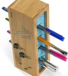 A wooden box filled with pieces of rubber to hold pens, pencils, or paintbrushes in place.