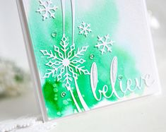featuring the beautiful Snowflake Ribbon Die and Fancy Believe die from Poppystamps! I started by wetting my whole piece of watercolor paper liberally and then I just dabbed green watercolors along the bottom left corner. I only used one shade of green and I just let that spread with the water. After it was very dry, I cut out the Snowflake Ribbon die out of white card stock, and glued that along the right side with Mono Adhesive. I cut the Fancy Believe die out...