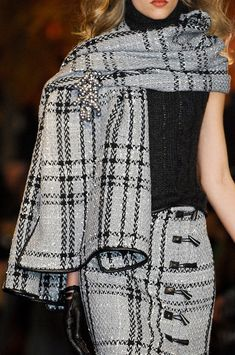 Douglas Hannant - grey & black plaid skirt with matching shawl.  Love the trim, the brooch, and the pairing with a sleeveless turtleneck, and gloves.