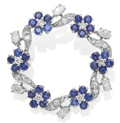 An 18 carat gold sapphire and diamond brooch, 1976. Designed as a wreath of circular-cut sapphire and diamond flowerheads, interspersed by a diamond-set undulating ribbon, with marquise-cut diamond foliate accents, London hallmark for gold, 1976, diamonds approximately 1.20 carats, sapphires approximately 2.00 carats, diameter 3.4cm