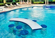 Build in table and chairs in pool.  I'd prefer a round table with maybe a hole in the center for an umbrella?