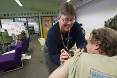 Pima County Health Department Library Nurse Jane Froemel gives Timothy Matthew a flu shot at the Pima County Public Library South Tucson Sam Lena Branch last year. Photo by Pima County Communications