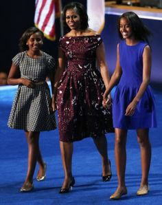 While her husband took the podium, she wore a well-tailored burgundy floral-printed dress by up-and-coming African-American designer Laura Smalls with an Alexis Bittar flower pin on her lapel.