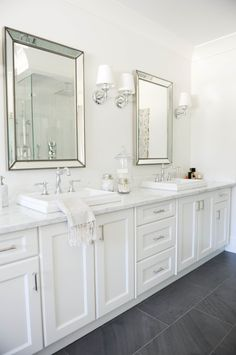 airy all-white bathroom with marble counters and white cabinets