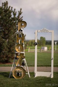 Salvaged screen door makes great frame to stand behind in this great photobooth vignette. Salvaged orchard ladder holds metal letters spelling PHOTO and vintage camera collection. #photobooth, #rusticwedding, #junkchic5280