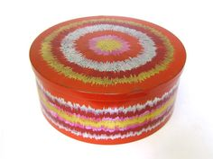 This gorgeous red storage tin with sunburst-like rings of gold, silver and pink was designed by Anita Wangel for Ira Denmark in the 1970s. The