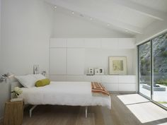 The master bedroom exemplifies the home's aesthetic: minimalist and light-filled, with the same white-oak flooring and custom millwork.