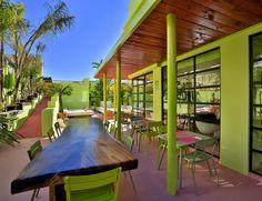 El verde pistacho protagoniza la terraza, con mesas de madera pulida y techo con cubierta de teca. Hotel Tropicana Ibiza Coast Suites