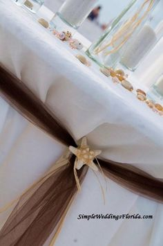 Unity table topped with sea shells and tied back with brown tulle and a white starfish
