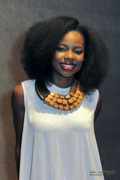 Pretty naturalista workin' a stretched out 'fro + chunky wood necklace + sleeveless white shirt