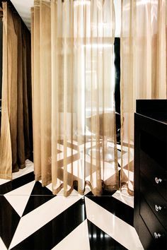 The decor of this modern elegant beauty salon creates a sense of luxury through the use of black and white tile patterns.  The interior design is sophisticated with its use of bronze sheer curtains to create private treatment rooms. Other decor ideas are the use of sleek styling stations giving a boutique hair salon ambiance. I #geometric | #storage | #drape |