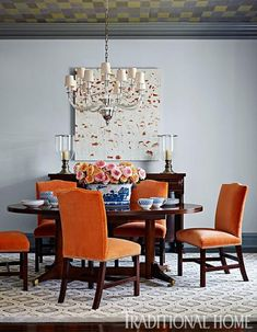 Fearless color abounds in this dining room with orange chairs, a ceiling covered in multi-colored wallpaper, and a light-blue-and-cream rug. - Traditional Home ® / Photo: Lucas Allen / Design: Andrew Howard