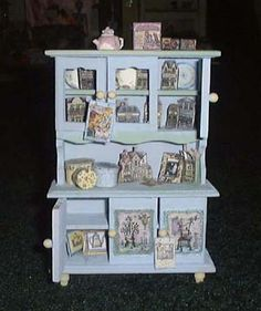 "This is one of those little miniature hutches they sell at a Michael's for $1. Spruced up with a little paint and some 'reproductions' of the ""Brandywine"" houses I collect and some other paper printies from different miniature sites on the web and you'd never know it started out so cheap. I did BTW make the little teapot on top  myself out of polymer clay ^^"