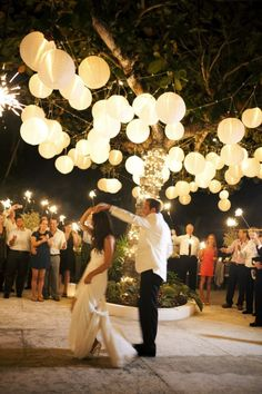 Hanging paper lanterns from a tree is a great way to create light and a dance floor for any outdoor reception.