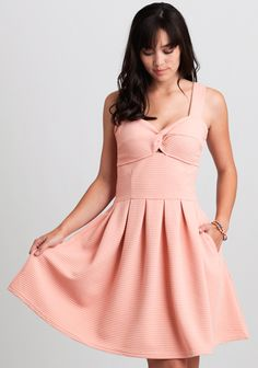 We absolutely adore this light pink fit-and-flare dress featuring a textured striped design and twisted knot detailing at the bust for a chic look.