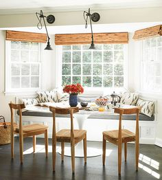 Mix High and Low-Update your kitchen, even if money is tight, by mixing high-end and low-end accessories into your breakfast area. This bay window bench breathes new life into this kitchen thanks to the clever coupling of a modern tulip table with rustic wooden chairs and inexpensive throw pillows.